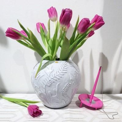 Vit Globo-vas från Nittsjö keramik, fylld med rosa tulpaner. Flankeras av rosa Ballograf deskset.