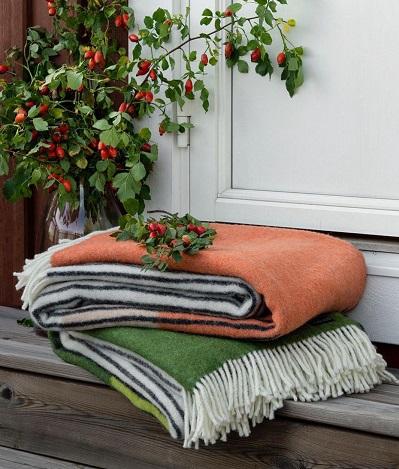 Yllefiltar Draw i orange-svart och grönt-svart från Design Lina Johansson, fotade på en trapp av trä mot vit dörr. Kvistar med höstbär i bakgrunden.